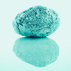 crumpled aluminum foil ball in egg shape on plain background, sweet tone instragram like process