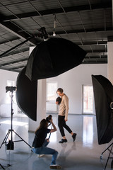 Photographer and model during studio session. Unrecognizable woman taking shot of male model in studio. Photo school, lookbook, fashion backstage concept