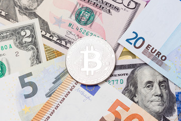 Golden Bitcoins close-up. Euro and dollars currency as a background.
