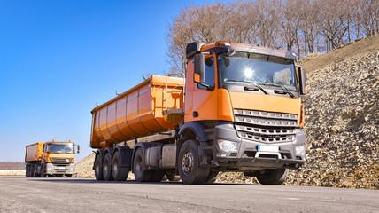 Zwei orange  LKW`s liefern Baumaterialien für eine neue Straßendecke