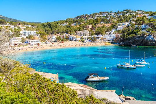 Fishing and sailing boats on blue sea water in Cala Vadella bay, Ibiza island, Spain