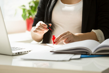 Closeup of young businesswoman painting fingernails at office table