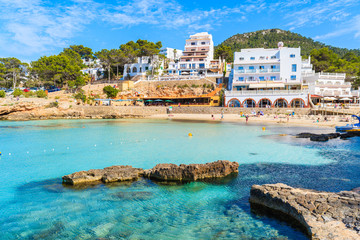 Hotel and restaurant buildings in Cala Portinatx bay with azure blue sea water, Ibiza island, Spain
