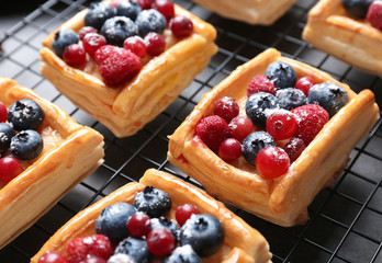 Fototapeten Brot Delicious puff pastry dessert with berries on baking grid, closeup