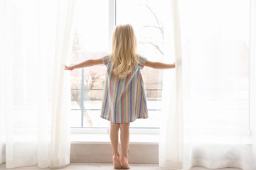 Small girl opening curtains