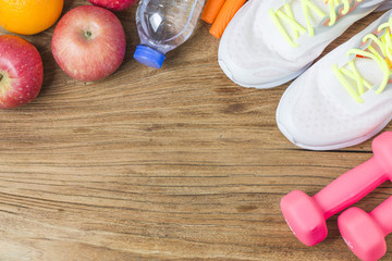 Fitness, healthy and active lifestyles Concept, Bottle of water, dumbbells, sport shoes, smartphone with headphone and apples on wood background. copy space for text. Top view
