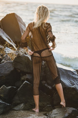fashion model posing on rocks near the sea