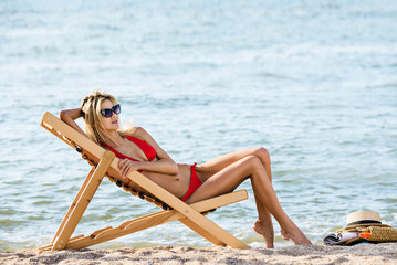 woman on the beach is relaxing on chaise-lounge