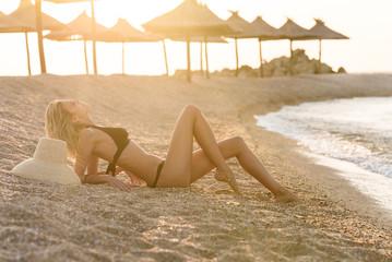 Blonde woman in bikini lays on the beach and has sunbathe
