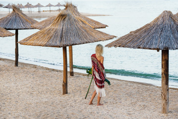 A girl on vacation, under an umbrella andholding palm leaf back view. Evening