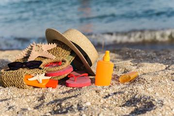 bag, suncream, glasses, flip flops on beach