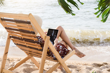 Lady on the seaside with tablet using internet