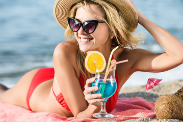 Attractive smiling woman is drinking exotic cocktai blue Lagoonl on the beach. Lays on sand