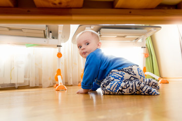 9 months old baby boy crawling under the bed at bedroom