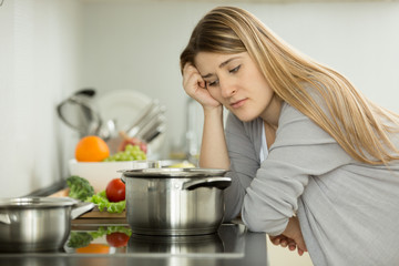 Portrait of upset woman cooking soup on kitchen