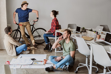 Cheerful young coworkers having interesting discussion