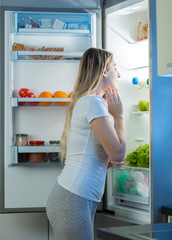Hungry woman looking inside open fridge at late night