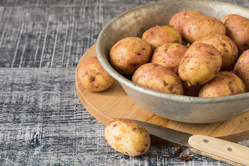 Potatoes. Young early potatoes in an old metal bowl on a wooden background.