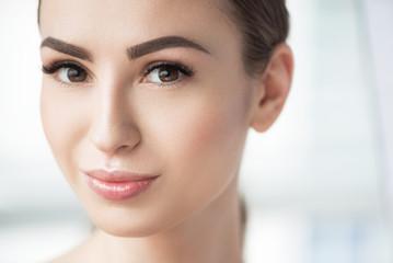 Joyful beautiful girl with perfect facial cosmetics
