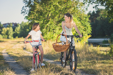 Young mother cycling with daughter riding to picnic