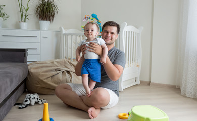 Happy young father playing with his 9 moths old baby boy on floor