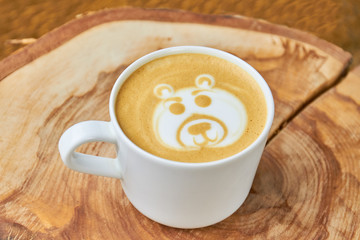 Bear coffee foam art. White cup with latte.