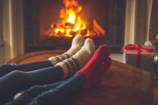 Family in cosy knitted socks warming at fireplace decorated for Christmas