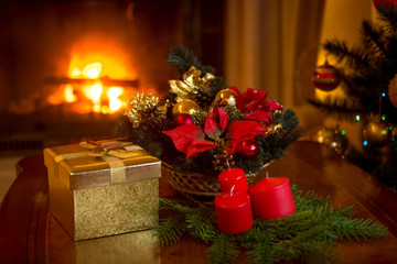 Beautiful Christmas tree and stack of presents in front of burning fireplace
