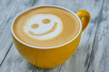 Smiley face latte art. Yellow cup with coffee drink. Effects of caffeine on mood.