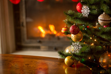 Wooden table in front of decorated fireplace and Christmas tree. Place for text. Suitable for Christmas background.