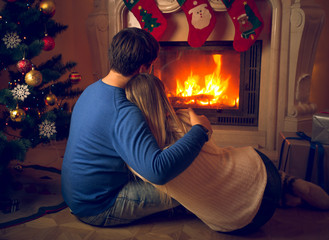 Couple in love sitting on floor and looking at fireplace and decorated Christmas tree