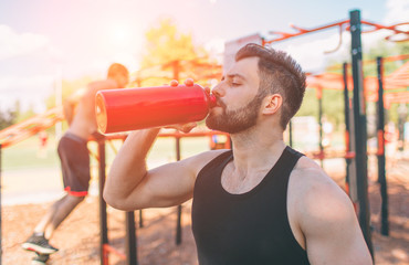 Man holding iron bottle and drinking water. Young handsome well formed sporty man resting after training outdoors. Male fitness model training workout