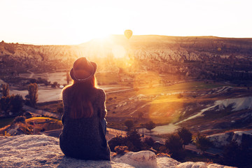 A tourist girl in a hat sits on a mountain and looks at the sunrise and balloons in Cappadocia. Tourism, sightseeing, Turkey.