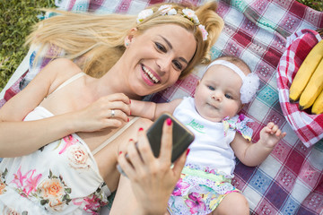 Happy mother and baby girl taking a selfie with mobile phone while laying on picnic blanket.