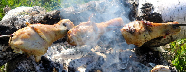 Chicken legs on a skewer over a fire.