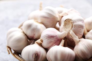 Garlic in basket on grey wooden table