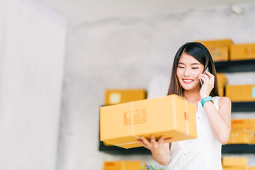 Small business owner, Asian woman hold package box, using mobile phone call receiving purchase order, working at home office. Online marketing delivery, startup SME entrepreneur or freelance concept