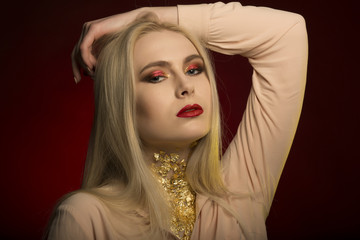 Wonderful young woman with perfect makeup in red color and gold foil on her neck
