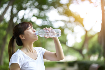 Sporty girl drink water after running in park