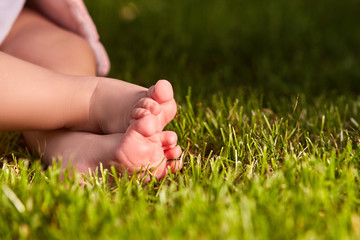Close up of baby's feet on the green grass on the meadow at warm day.