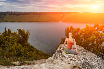 Beautiful woman is practicing yoga on the rock above big river against sky.