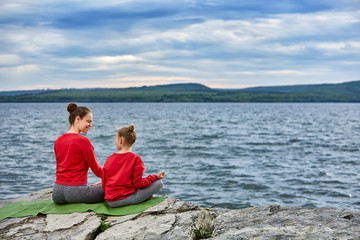 Rear view of the mother and daughter are practicing yoga on the rock near river.