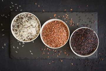 Assorted of variety of gourmet rice in bowls On black background. Top view