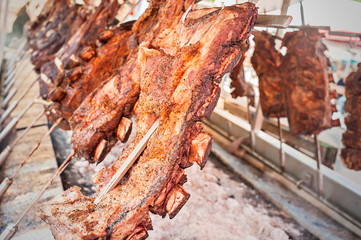 Roasted meat of beef cooking. Asado is traditional Argentine dish.