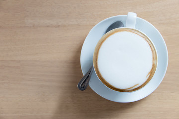 Hot cappuccino in white cup on wooden table with copy space