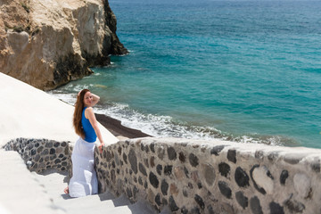Young woman on the stairs down to the White beach, Santorini, Greece