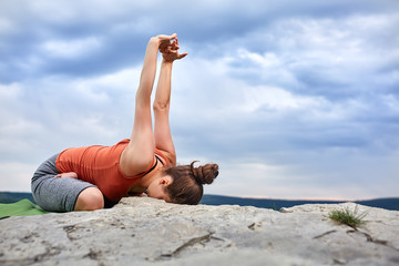 Attractive woman making yoga exercise on the big stone against beautiful river.