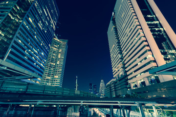 Photo of commercial office buildings exterior. Night view at bottom skyscrapers with light of traffic rush, long exposur in Bangkok
