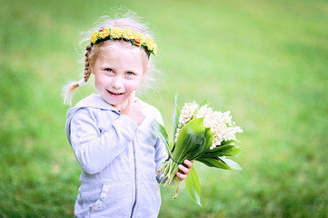 Half length portrait of smiling baby girl with spring flowers