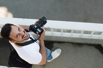 Portrait of young professional man with camera shooting outdoor